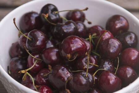Fresh cherry on plate on wooden blue background.  Sweet cherries. Stock Photo