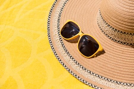 Hat and sunglasses. On yellow background. Summer holiday and travel concept. Copy space background, top view flat lay overhead. Summer vacation.