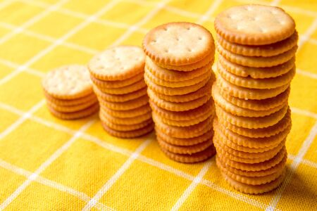 Stack Of Crackers. Pile Column. Cookie cracker. yellow tablecloth. Stock Photo