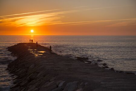 Sunset every day with people. People in Atlantic Ocean. Beautiful sunset.