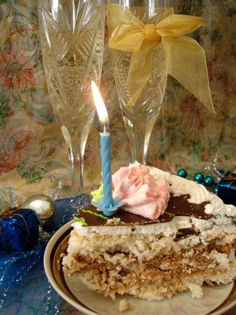 celebratory table (piece of birthday cake and blue candle, two glasses with champagne, gift boxes) Stock Photo - 763804