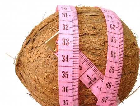 coconut with pink tape measure over white background (concept of health, diet)  photo