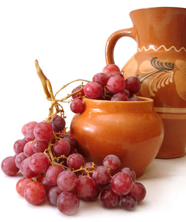 jug and red grapes over white background  Stock Photo