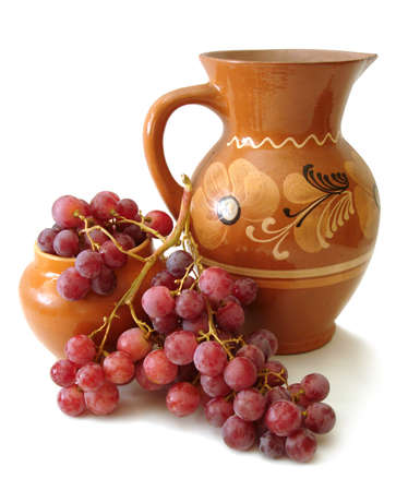 jug and red grapes over white background  photo