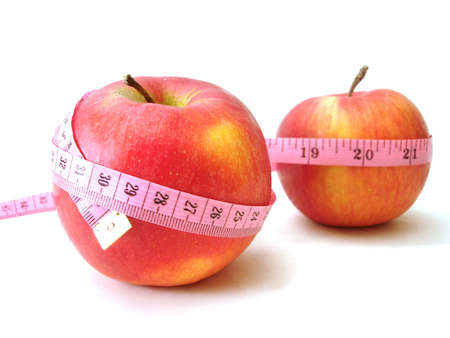 scrawny: apples with pink tape measure over white background (concept of health, diet)  Stock Photo