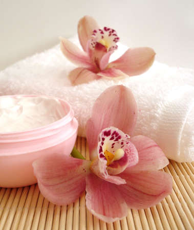 Spa essentials (violet salt, white towel and pink orchids)  Stock Photo