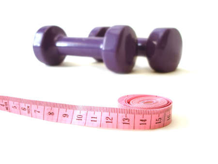 scrawny: pink measuring tape and violet rubber dumbbell over white background