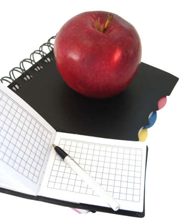 opened notebook with pen and red apple  photo
