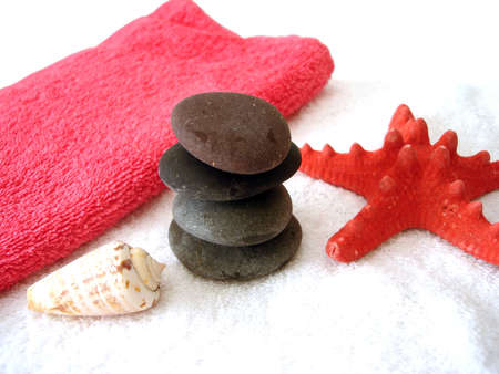 stone wash: Spa essentials (pyramid of stones with white towel and seashell)