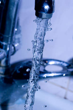 water  running down from faucet in blue color  photo