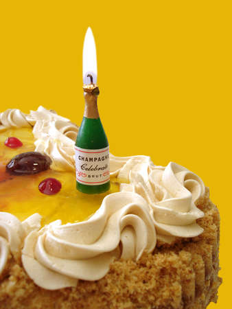 birthday champagne: birthday cake with candle on yellow background (bottle with champagne)  Stock Photo