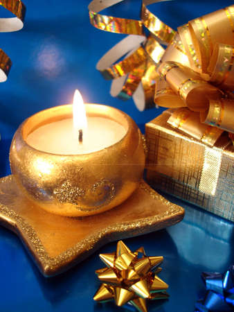 golden candle and gift box on blue background Stock Photo - 2167235
