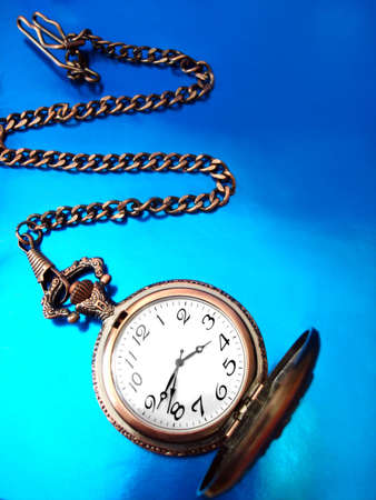 close-up of old golden clock on blue background  photo