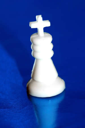 gamesmanship: white chess king stands on blue background  Stock Photo