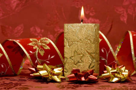 golden candle on red background Stock Photo
