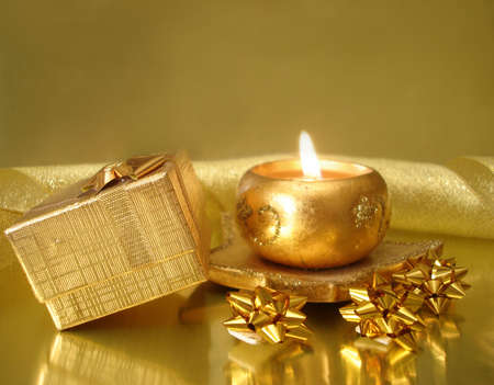golden candle and gift box on celebration background