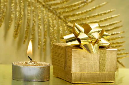 golden gift box and burning candle  photo