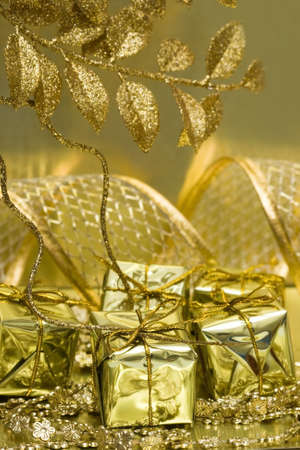 adorning: gift boxes on golden background with leaf  Stock Photo