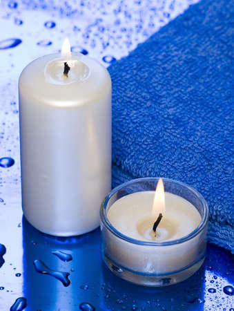 spa essentials, candles and towel on blue background  photo
