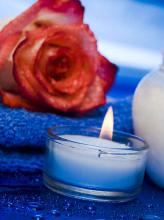cream, candle with rose on blue background  photo