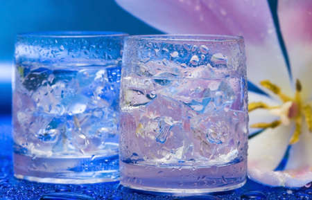 Glasses with water and flower over blue  photo