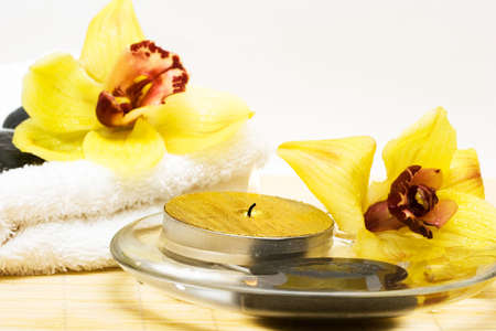 stone wash: candle in water with yellow orchids and towel
