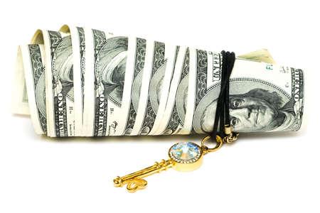 golden key and dollars isolated on white  photo