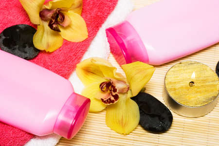 candle, bottle of shampoo with stone and orchid  photo