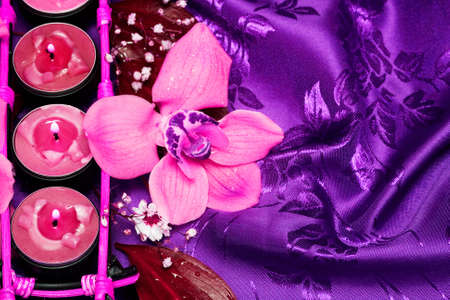 Row of pink candles and orchids  photo