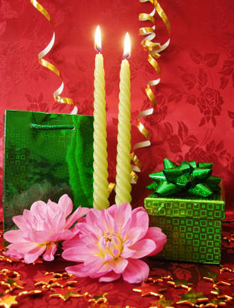 celebration table (candles; flowers and gift on red background)  photo