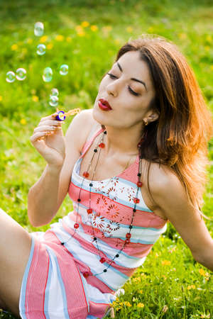 inflating: girl inflating soap-bubbles in field   Stock Photo