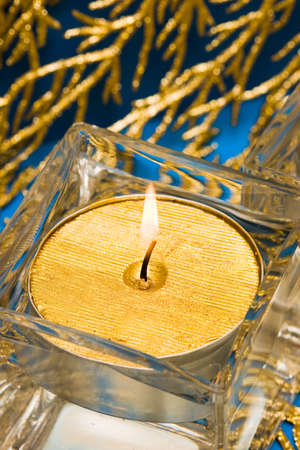 golden candle in glass with water  photo