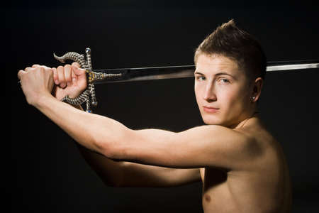 sabre: man with sword on black background   Stock Photo