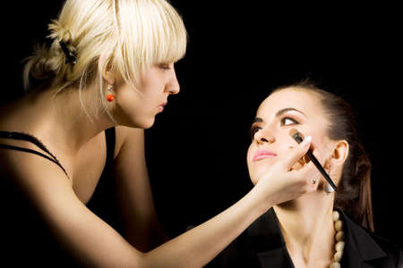 cosmetologist doing make-up for model with brush  photo