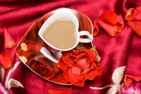 red cup of coffee with rose  photo