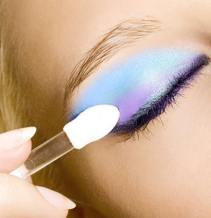 close-up of young beautiful girl make her make-up with brush  photo