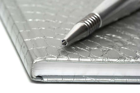 silver pen with closed notebook  photo