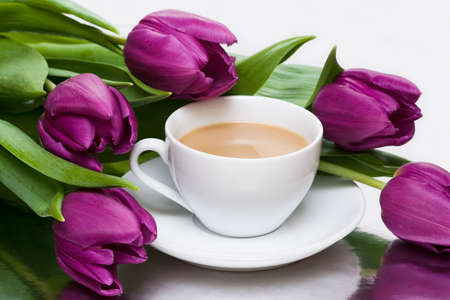 aqua flowers: white cup of coffee with violet tulips
