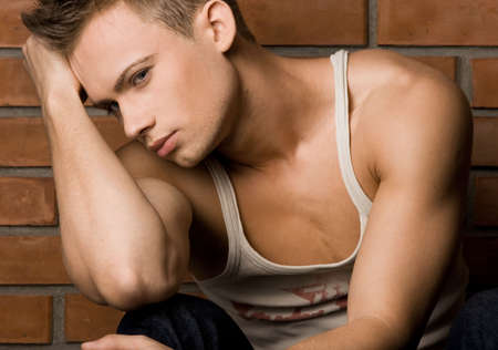 muscle shirt: el hombre de moda, cerca de la pared