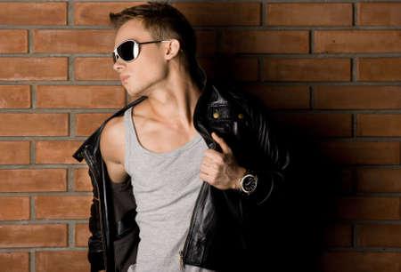 muscle shirt: fashionable man near the wall