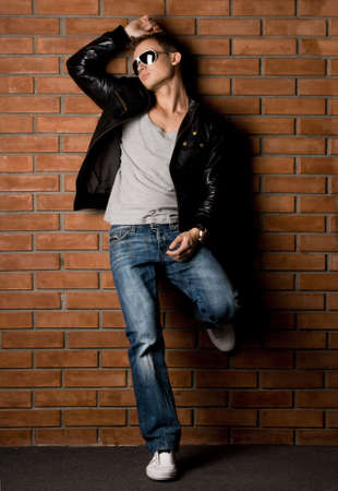 modelos hombres: moda hombre cerca de la pared  Foto de archivo
