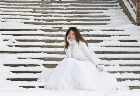 Bride in winter near the stair photo