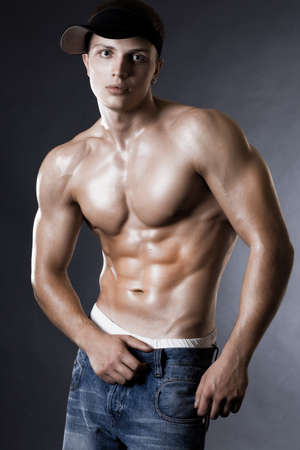 strong boy: young bodybuilder man on black background Stock Photo