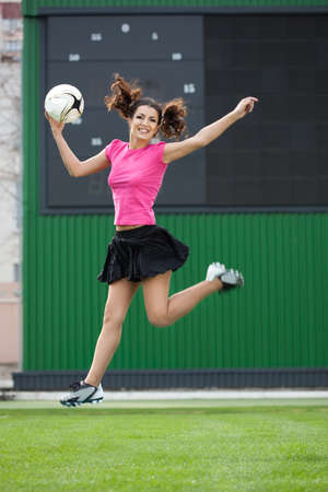girl cheerleaders jumping with a soccer ball photo