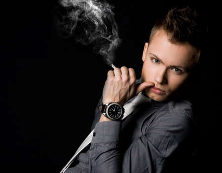 male fashion model: hombre de negocios atractivo con un cigarrillo