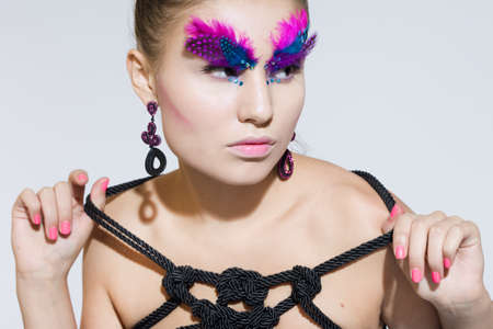 Beautiful fashionable woman with feathers photo