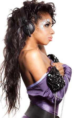 mulatto girl DJ listens music with headphones Stock Photo