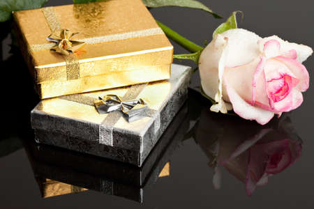 gift boxes with rose on black background photo