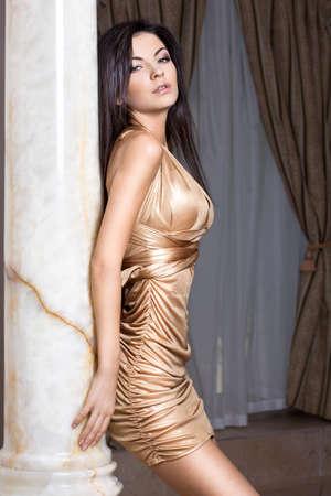 beautiful fashionable woman near the column photo