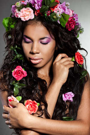 Elegant mulatto girl with circlet of flowers photo